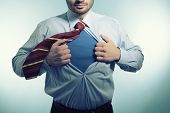 Super hero. Business man opening his shirt like a superhero, over blue background
