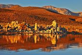 Blazing orange sunset at Mono Lake.  Yosemite National Park, USA. Outliers -  bizarre calcareous tufa formation  reflected in the mirrored surface of the water