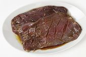 picture of flank steak  - Two pieces of marinded flank steak resting on a plate prior to grilling - JPG