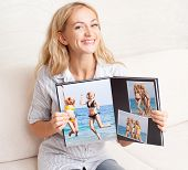 Young woman showing photo book. Female with photography album