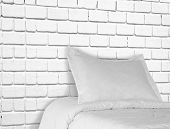 white bed against brick wall.