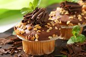 two delicious muffins with chocolate curls and sprinkled with nuts