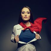 Young pretty woman opening her shirt like a superhero. Super girl, image toned. Beauty saves the wor
