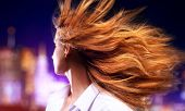 Young woman shaking hair. On night city background.