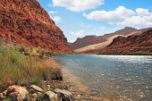 Clean and clear water of the Colorado River among the steep mountains of red sandstone.