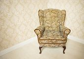 Stylish empty upholstered gold vintage armchair standing in the corner of a room with wallpapered wa