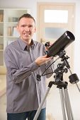 Man with astronomical telescope standing near a window with eyepiece in hand