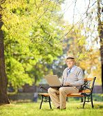 Senior gentleman working on laptop seated on bench in park looking at camera, shot with a tilt and s
