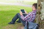 Student using his tablet pc outside on college campus