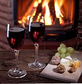 Romantic still life near the fireplace. Glasses of wine, cheese and nuts.
