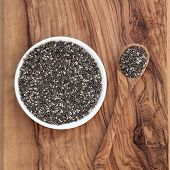 Chia seed healthy super food over olive wood background. Salvia hispanica.