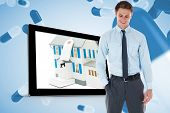 Smiling businessman standing with hand in pocket against blue pills floating
