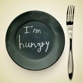 picture of a fork and a plate painted as a blackboard with the text I a??m hungry written in it on a beige background with a retro effect