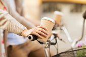 summer holidays, bikes, love, relationship and dating concept - closeup of woman hand holding coffee and riding bicycle