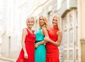 holidays and tourism, friends, hen party and blonde girls concept - three beautiful women in the cit