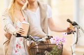 summer holidays, bikes, love, relationship and dating concept - closeup of couple holding coffee and riding bicycle
