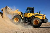 stock photo of hydraulics  - Bulldozer dumping stone and sand in a mining quarry - JPG