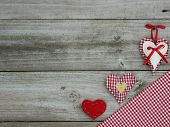 Red hearts and red gingham (checkered) tablecloth border wood background