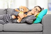 Young man holding teddy bear and taking a nap on couch, at home