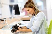 stock photo of 35 to 40 year olds  - Woman reporter in office looking at photo camera - JPG