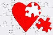A red heart jigsaw puzzle with a piece on the side, good image for a broken heart, love, romance and