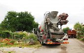 stock photo of revolver  - A concrete mixer truck delivering concrete to a small domestic building site in north east Italy - JPG