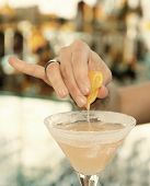 Female bartender is squeezing orange juice into a cocktail glass, toned, vignetting added
