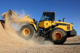 stock photo of bulldozers  - Bulldozer dumping stone and sand in a mining quarry - JPG