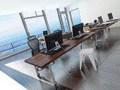 Modern minimalist coastal office overlooking the sea with a long office table with several computer workstations and a glass view wall