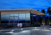 Contemporary luxury house with a glass facade and a curving swimming pool illuminated at night with