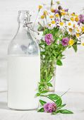 stock photo of milk-pint  - Fresh milk in old fashioned bottle and wildflowers on the wooden background - JPG