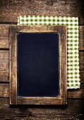 Blank Aged  Menu Blackboard Over Vintage Wooden Background With Tablecloth.