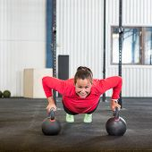 Portrait of young woman doing pushup exercise with kettlebell in gym