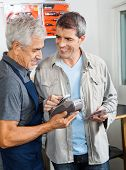 Senior man holding electronic reader while male customer paying through smartphone in hardware store