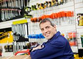 Side view portrait of mature worker leaning in hardware shop