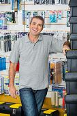 Portrait of happy mature man standing by stacked toolboxes in hardware store