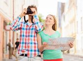 travel, vacation, technology and friendship concept - smiling couple with map and photo camera explo