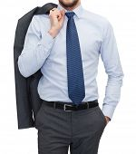 business and office concept - handsome buisnessman with jacket over shoulder