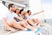 vacation, travel, sea, friendship and people concept - smiling friends sitting on yacht deck and poi