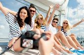 vacation, travel, sea, friendship and people concept - smiling friends sitting on yacht deck and pho
