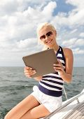 vacation, holidays travel, sea and technology concept - smiling woman sitting on yacht with tablet p