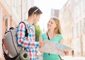 travel, vacation and friendship concept - smiling couple with map and backpack in city