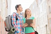 travel, vacation, technology and friendship concept - smiling couple with tablet pc and backpack in