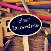 the sentence c'est la rentree, back to school written in french in a blackboard label, on a wooden t