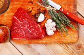 stock photo of flesh  - fresh raw beef meat fillet flesh with peppercorn and thyme ready to grill on wood figured old style board  over table with spices in glass - JPG