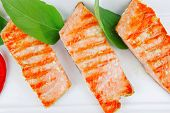 roasted salmon pieces with pepper and lemon on basil leaf over ceramic plate isolated on white backg