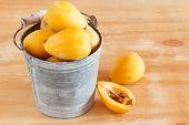 Loquat Fruit  In Bucket On Wooden Table