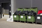 picture of garbage bin  - Green garbage containers near large food city shop - JPG