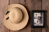 Closeup of a straw hat and a framed baby picture on a rustic wooden wall. Image can easily be replac
