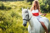 Beautiful sensual women riding on white horse